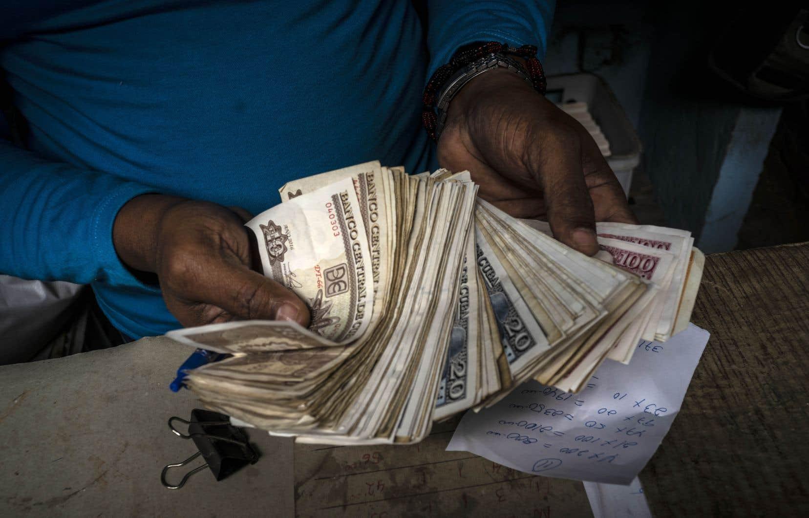 Un travailleur montrant une liasse de billets de la monnaie qui règne désormais à Cuba, le peso cubain (CUP)