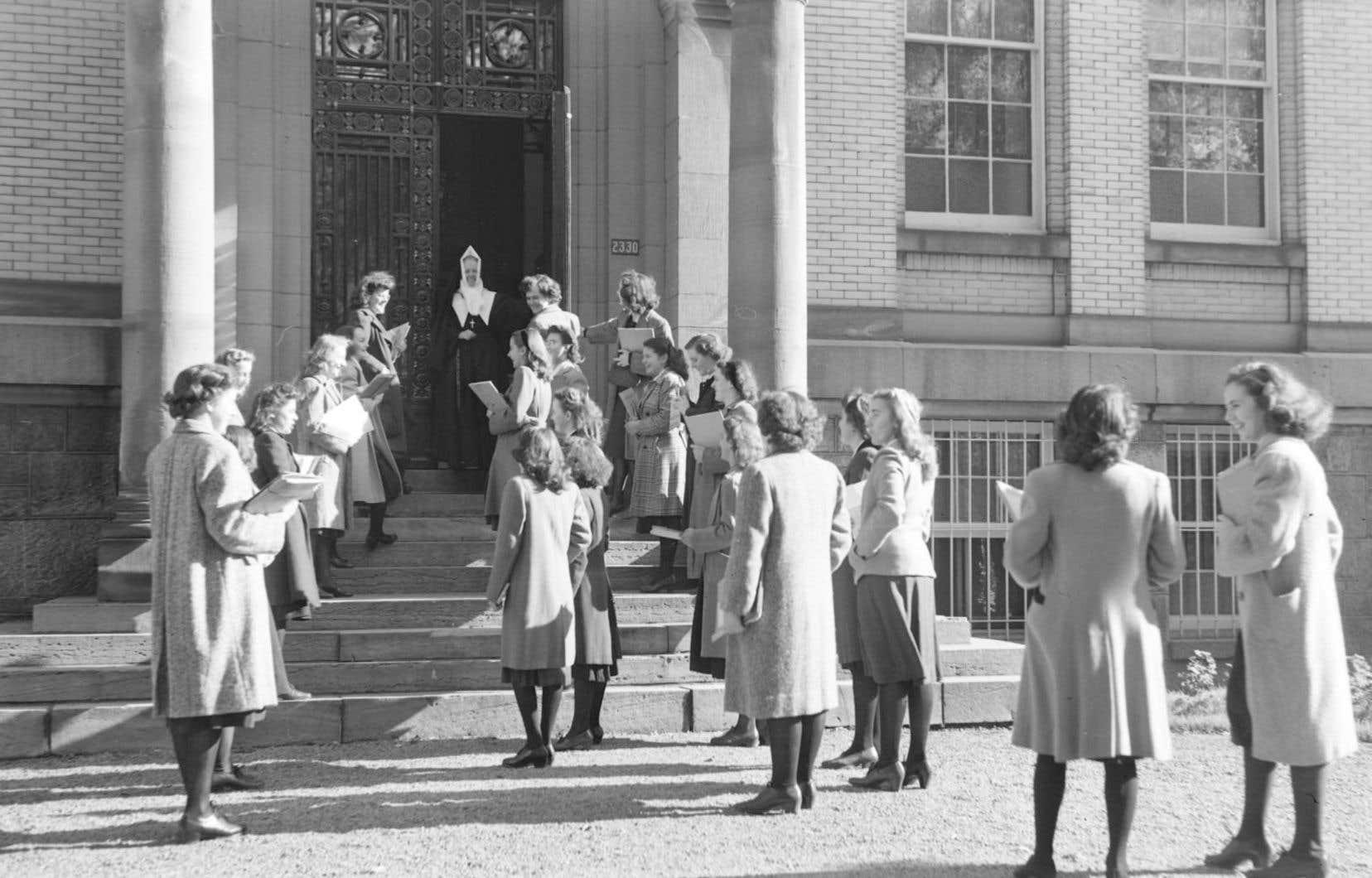 Une religieuse de la Congrégation de Notre-Dame accueille des jeunes filles à l'entrée de l'École normale Jacques-Cartier de la rue Sherbrooke ouest à Montréal.
