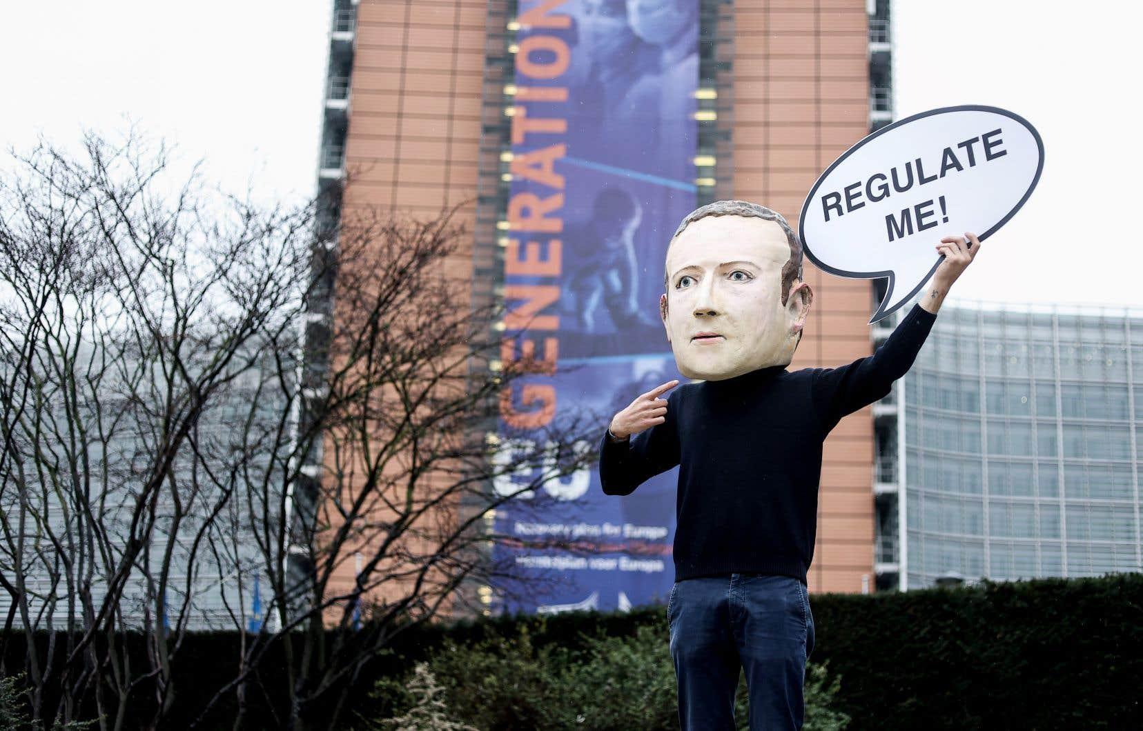 L'entreprise subit des pressions de par le monde pour payer plus d'impôts et mieux restreindre les discours haineux. En photo, un manifestant portant un masque à l'effigie du p.-d.g. de Facebook, Mark Zuckerberg, devant le bâtiment de la Commission européenne à Bruxelles en décembre 2020.