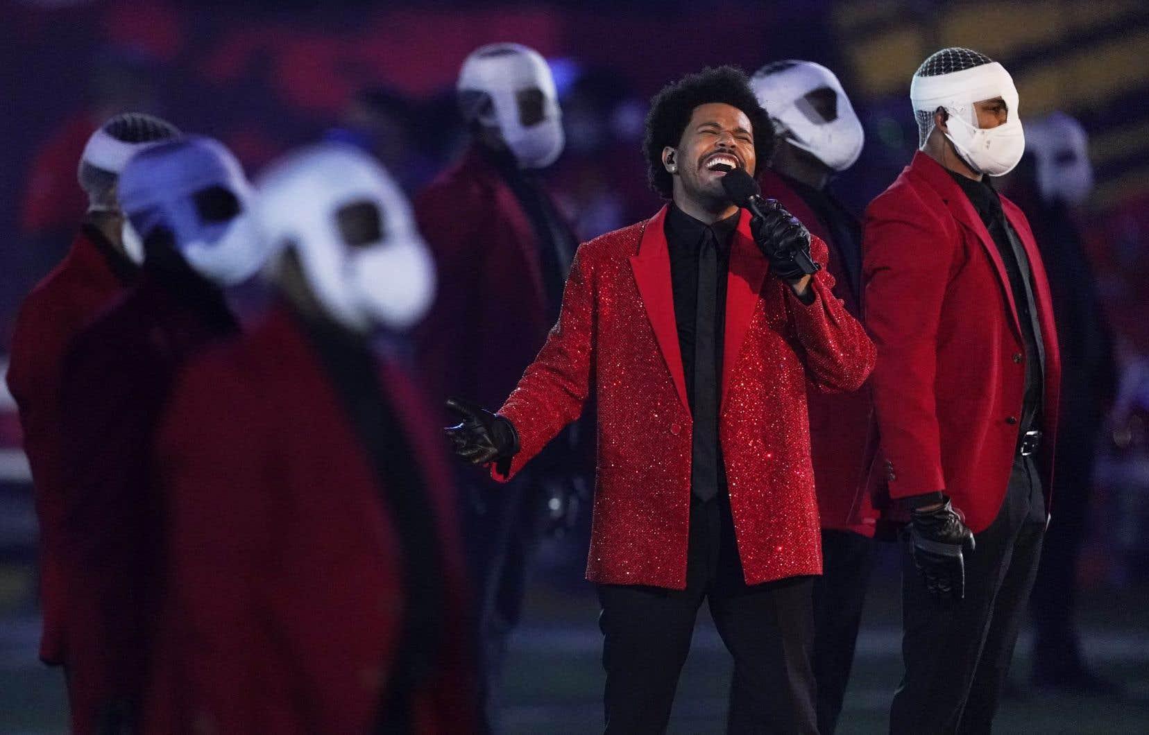 Une fois sur le gazon, le chanteur a lancé <em>Bliding Lights</em>, entouré de plus de cent danseurs habillés comme lui, recouverts de bandages sur le visage.
