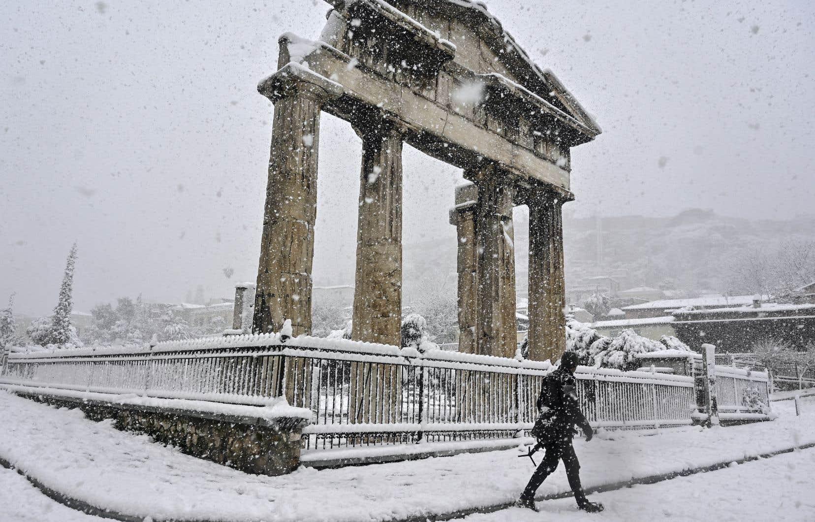 Un homme passe devant l'Agora lors de fortes chutes de neige sur Athènes, le 16 février 2021.