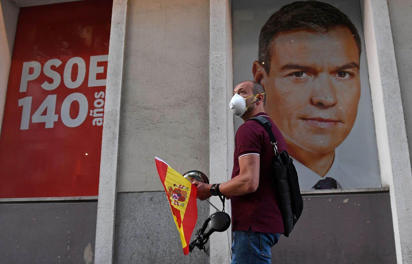 Un citoyen de Madrid devant une affiche du premier ministre Pedro Sanchez en mai dernier