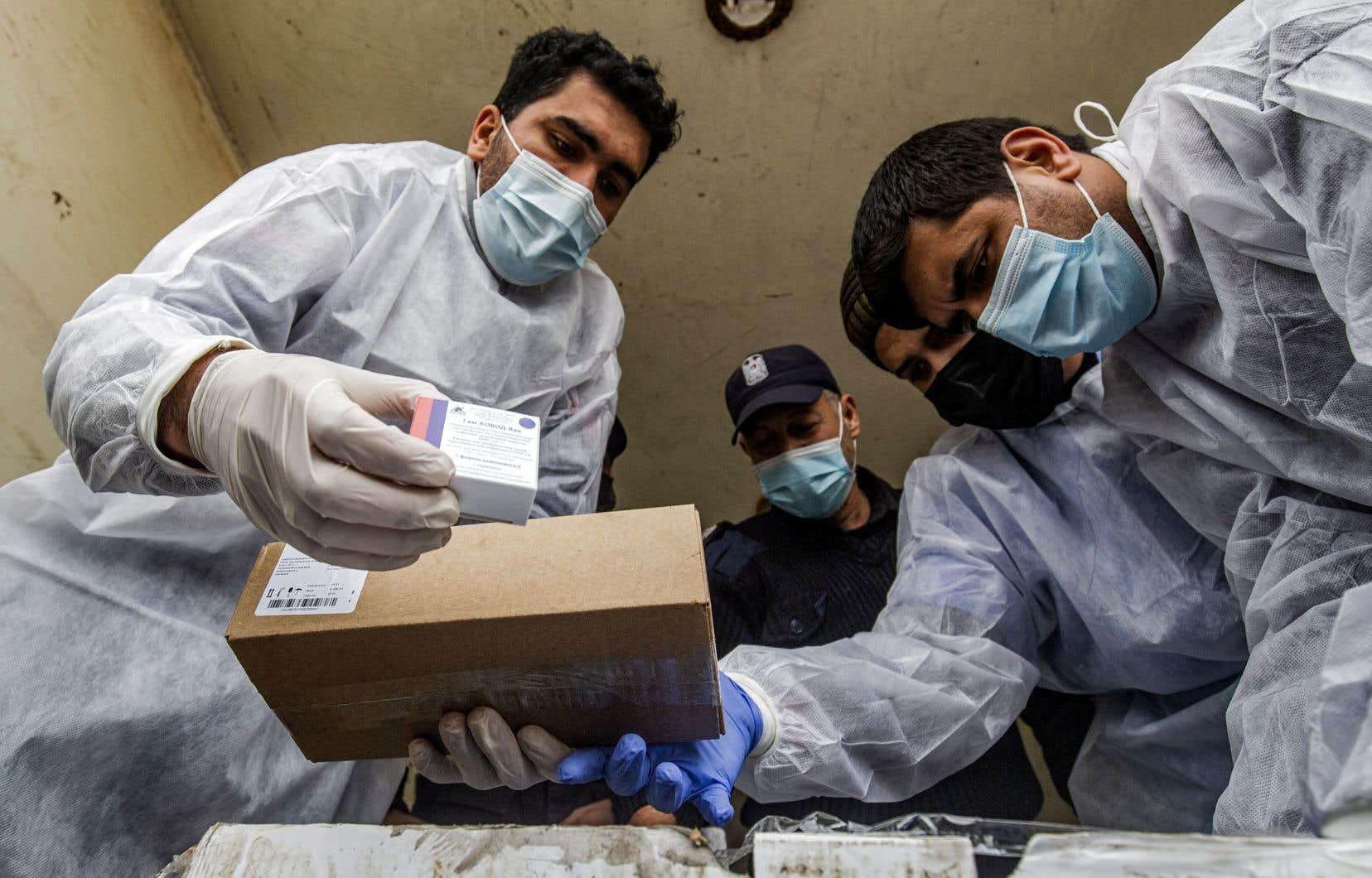 Des travailleurs de la santé palestiniens déchargent un premier lot de 2000 doses du vaccin russe Spoutnik V à Gaza, le 17 février 2021.