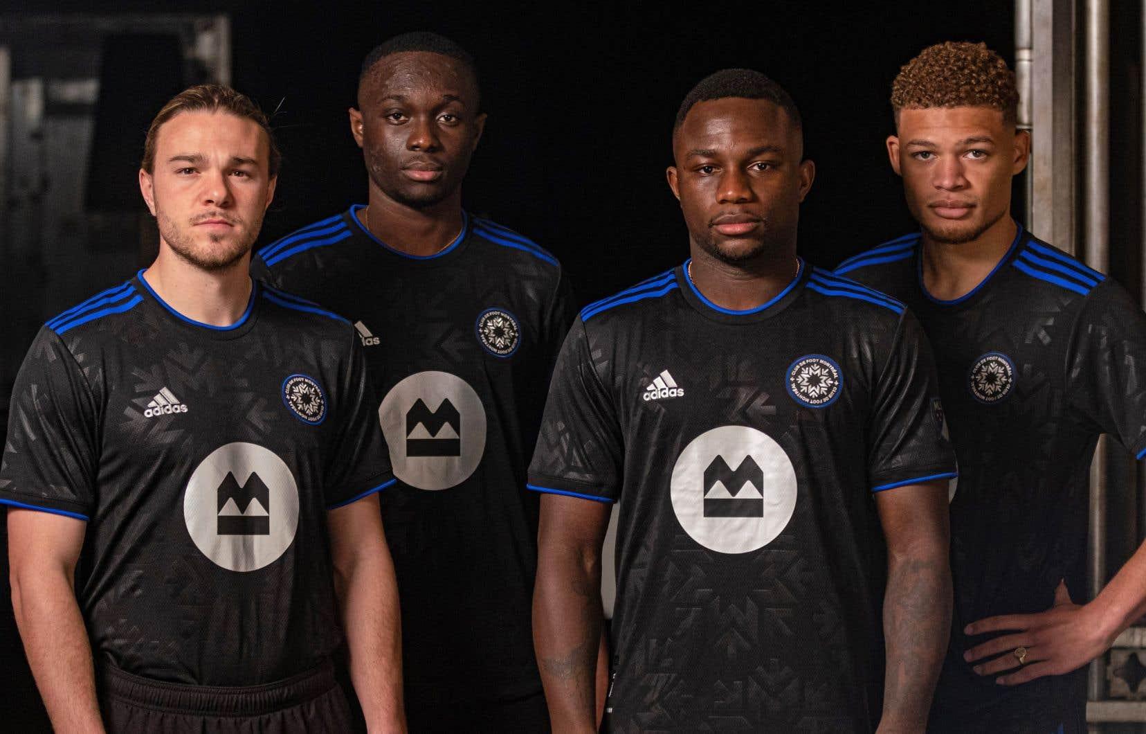 Le maillot noir est agrémenté de trois lignes bleues qui vont du col aux manches, ainsi que d'une bordure bleue autour du col et des manches.