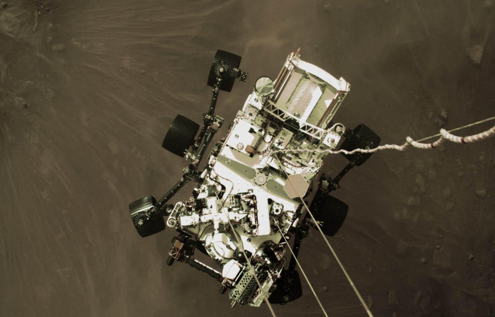 Cette photo publiée par la NASA montre l'astromobile «Perseverance» être peu à peu déposée au sol, suspendue par trois câbles,à la surface de Mars le 18 février 2021.