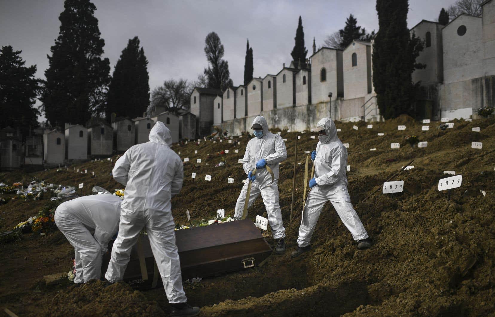 Depuis le début de la pandémie de COVID-19, en décembre 2019, pas moins de 112 618 488 cas d'infection au nouveau coronavirus ont été recensés sur la planète, dont 2 500 172 décès. Sur la photo, des employés d'un cimetière à Lisbonne, au Portugal.