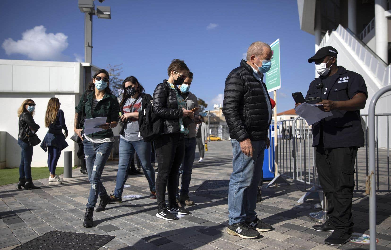 Des citoyens faisaient la file, brandissant leur certificat de vaccination, pour accéder à un concert à Tel-Aviv. Israël a récemment mis en place un système permettant l'accès aux salles de sport, aux théâtres et aux restaurants.