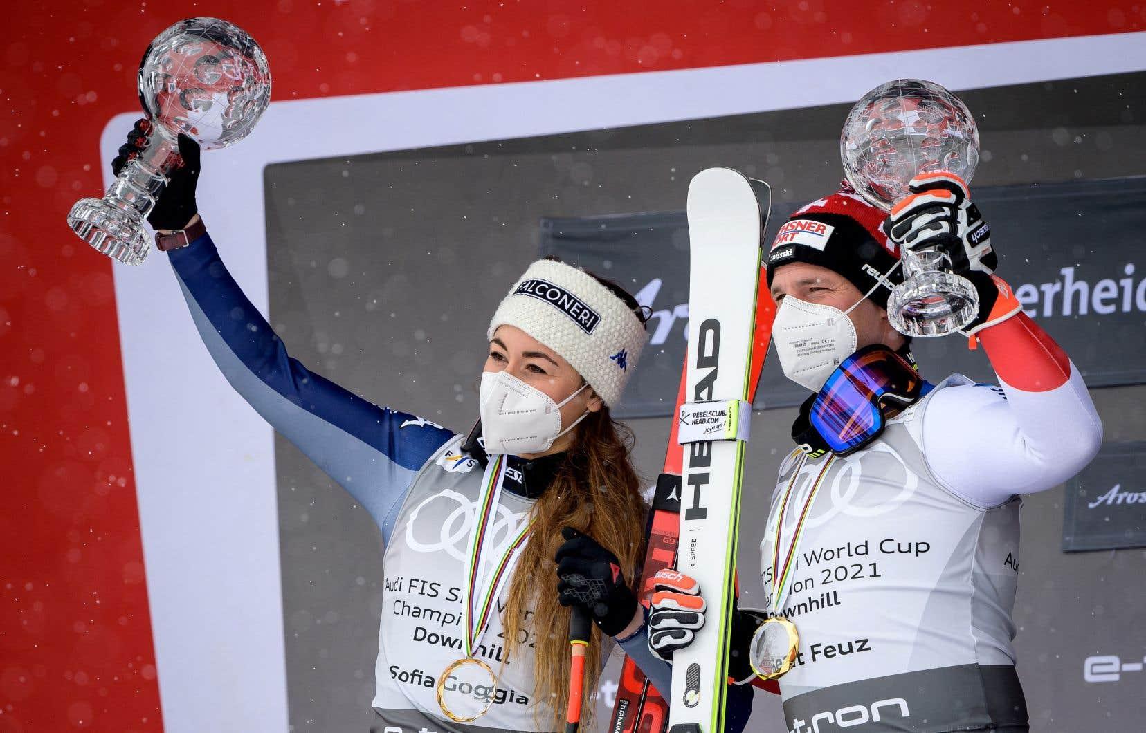 Le Suisse Beat Feuz et l'Italienne Sofia Goggia célèbrent sur le podium après avoir remporté le globe de cristal de la Coupe du monde de ski alpin pour la descente masculine et la descente féminine.