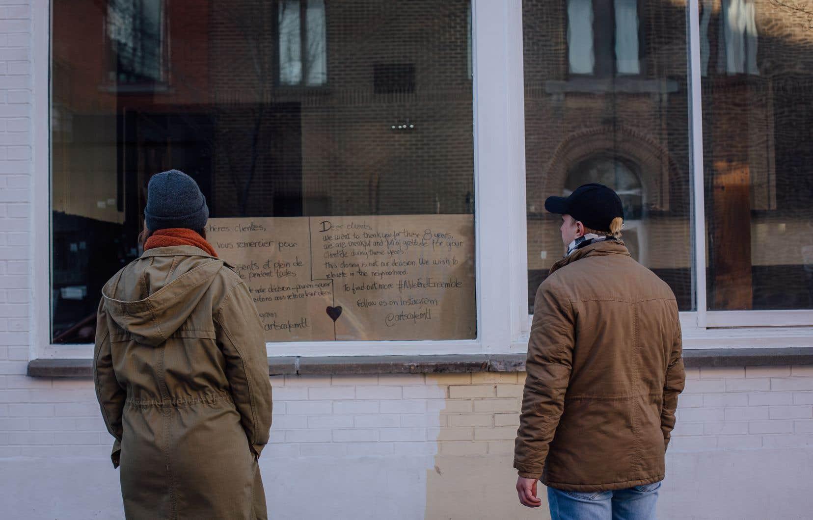 La fermeture récente de l'Arts Café, dans le Mile End, sème la consternation dans le quartier qui a perdu plusieurs commerçants dans les dernières années. Sur la photo, des passants lisent une note écrite à l'intention des clients par les anciens tenanciers du café.