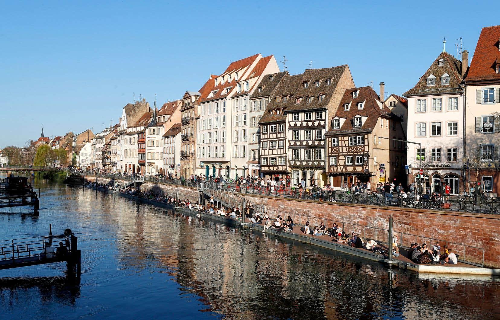 Des gens sur la rive de l'Ill à Strasbourg, en France. Le pays a donné mercredi un nouveau tour de vis contre la pandémie, à l'image d'autres pays d'Europe.