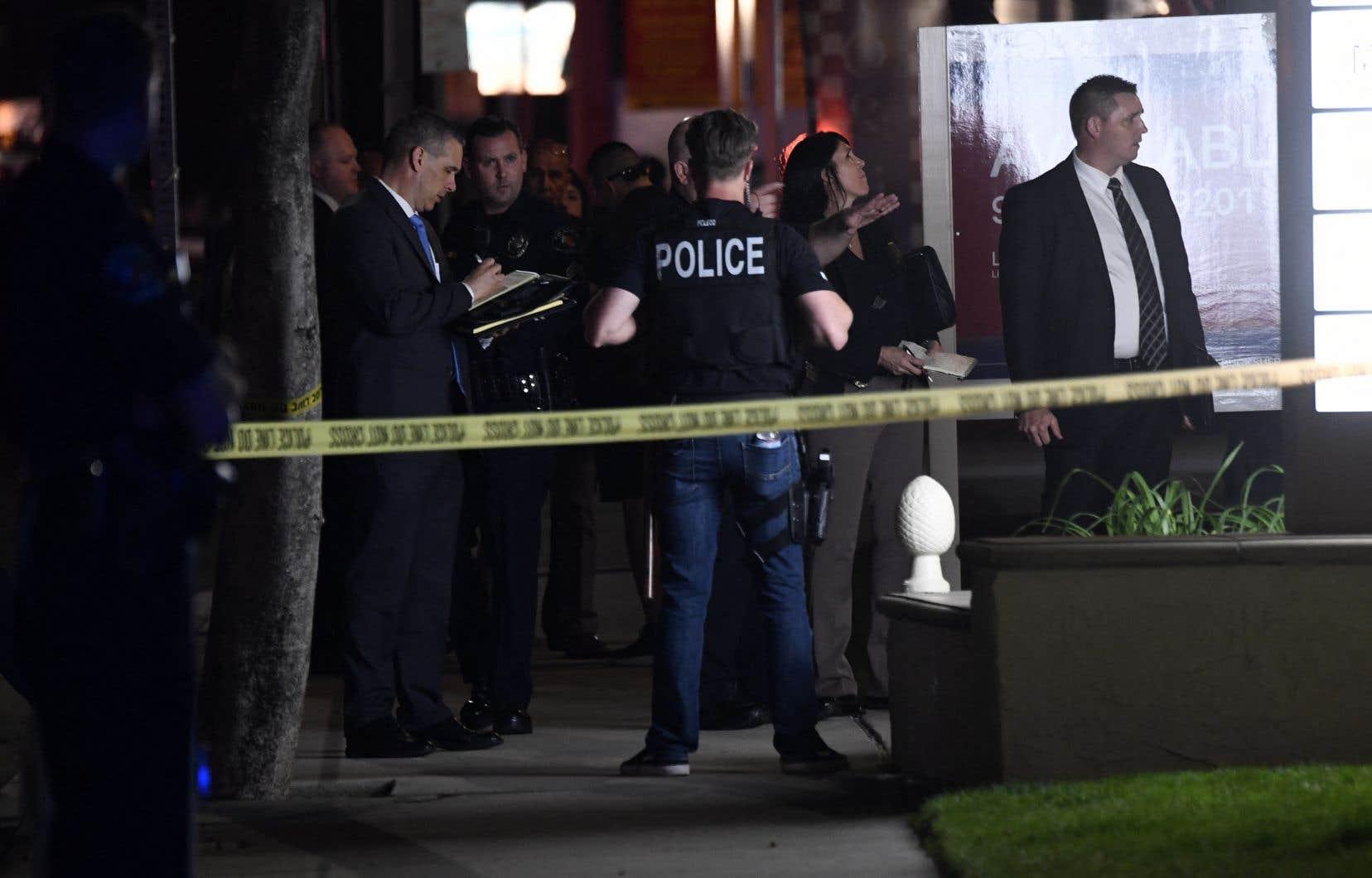 Des policiers et des agents se tenaient à l'extérieur de immeuble de bureaux où la fusillade s'est tenue à Orange, en Californie, mercredi. Les autorités ont déclaré que quatre personnes, dont un enfant, avaient été tuées.