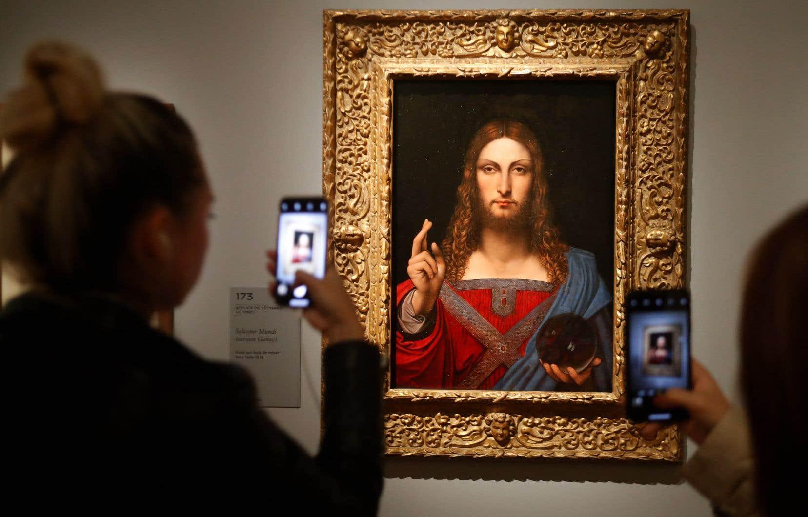 Des gens prennent des photos du «Salvator Mundi» de l'Atelier Léonard de Vinci, lors du vernissage de l'exposition «Léonard de Vinci», le 22 octobre 2019 au musée du Louvre à Paris.