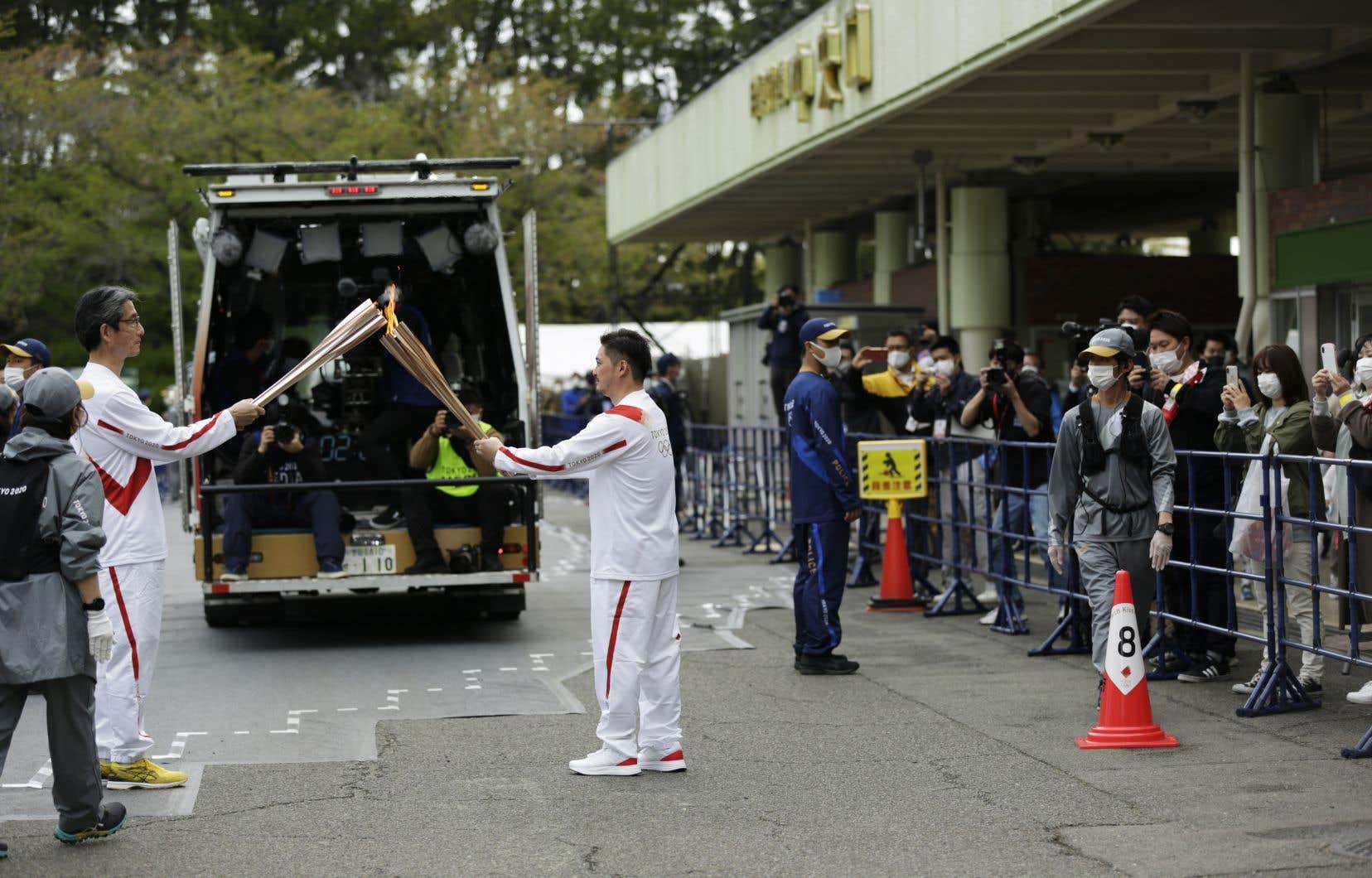 Des épreuves tests ont été reportées, le relais de la flamme olympique a été réduit au minimum et de nouvelles restrictions sanitaires sont en vigueur à Tokyo et dans d'autres villes nippones.