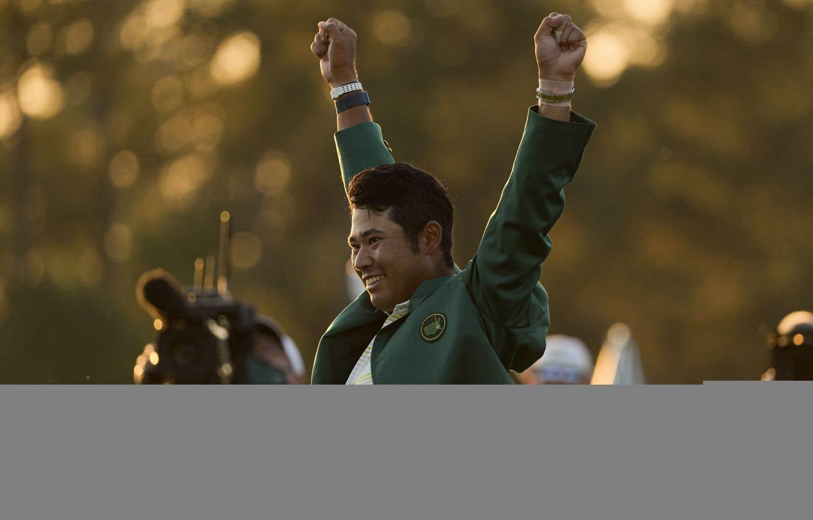 Le Japonais Hideki Matsuyama revêt la veste verte du champion après avoir remporté le tournoi de golf Masters dimanche, à Augusta en Géorgie.