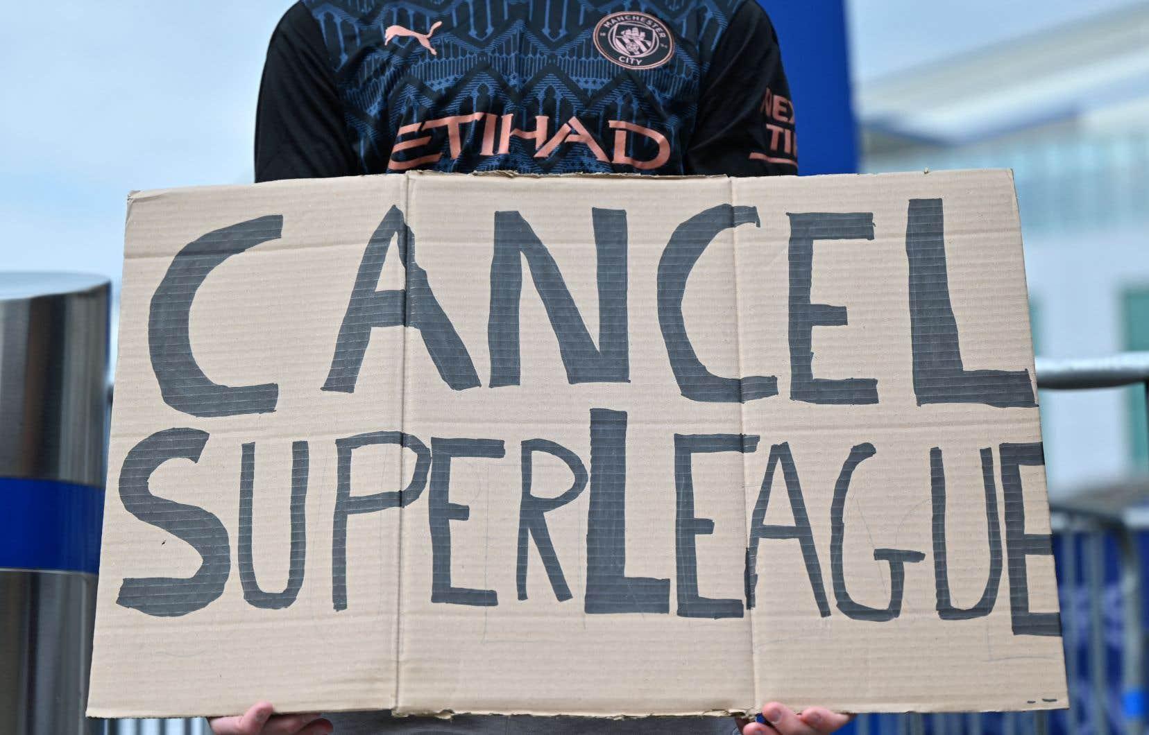 Un partisan de Manchester City brandit une pancarte contre le projet du club de se joindre à la Super Ligue.