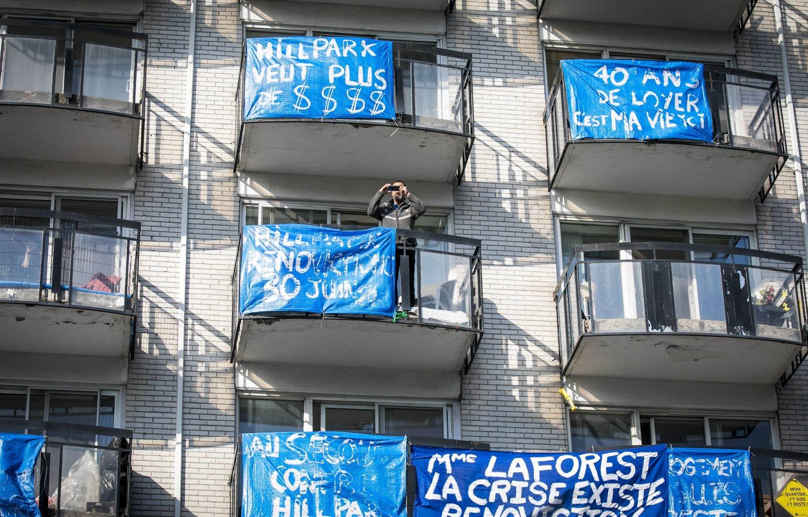 Un resident du Manoir Lafontaine prend une photo avec son cellulaire de son balcon durant un rassemblement du FRAPRU contre l'éviction de locataires du Manoir Lafontaine.