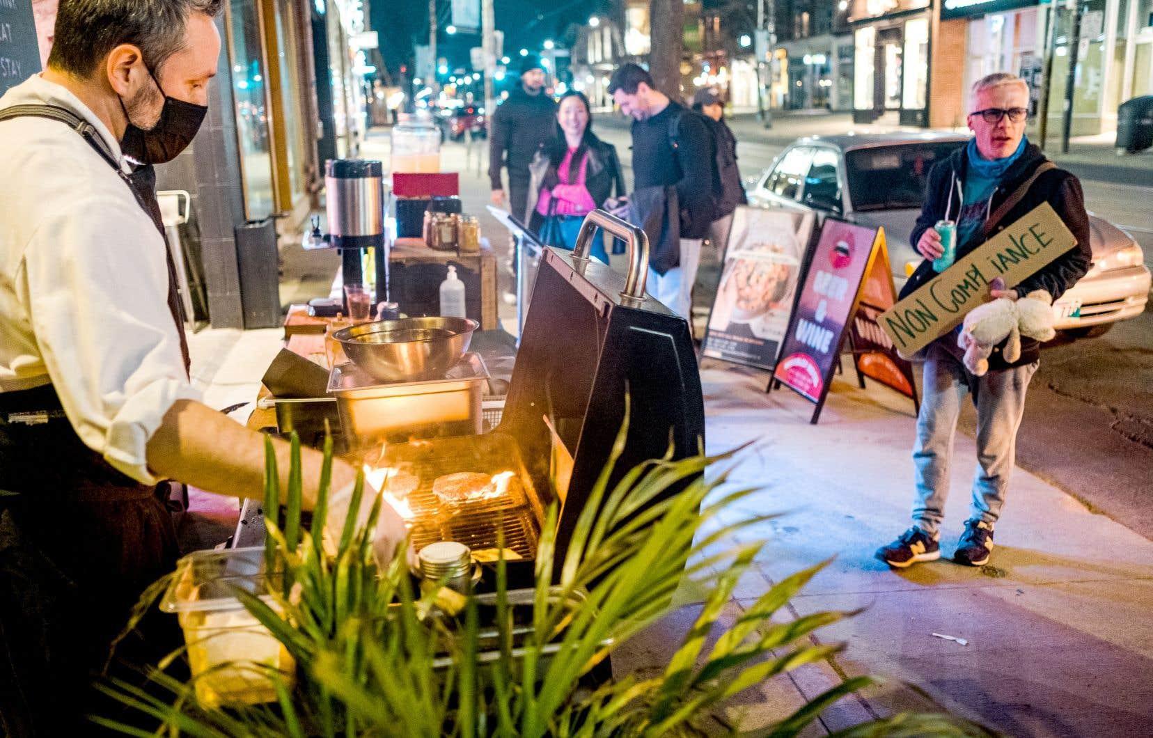 Bien campé derrière son barbecue qui obstrue partiellement le trottoir de la rue Queen Ouest, à 21heures passées samedi, Wesley Barber vend des hamburgers aux passants.