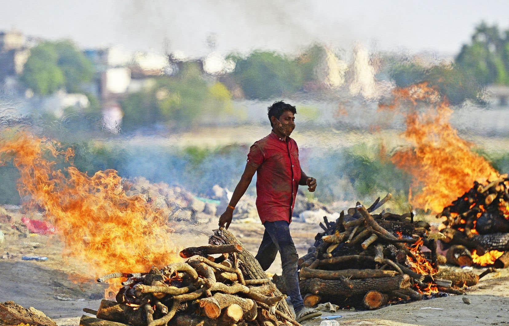 De nombreux crématoriums et cimetières en Inde affirment que le bilan officiel des décès dus au virus est loin de correspondre à la réalité, compte tenu de l'afflux de corps qu'ils voient défiler. Sur la photo, un crématorium à ciel ouvert, mardi à Prayagraj (anciennement Allahabad), dans le nord de l'Inde.