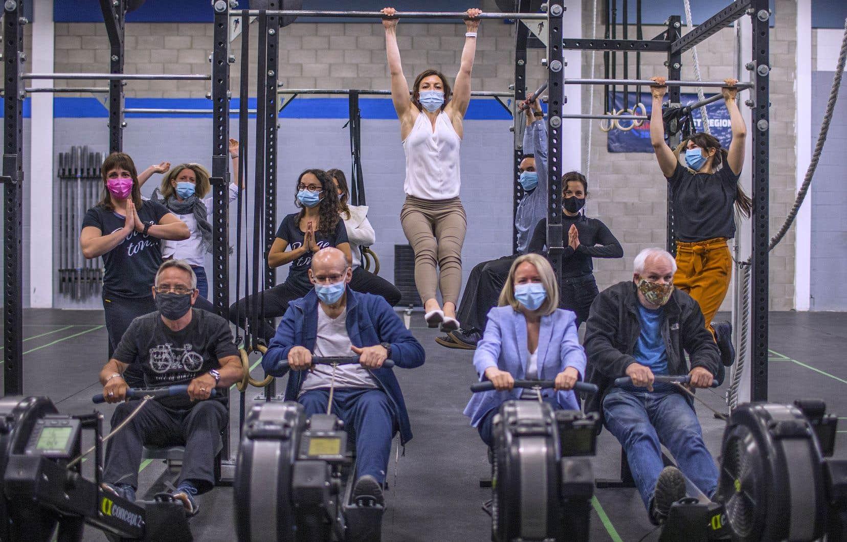 La Dre Anne-Isabelle Dionne (en blanc), entourée de son équipe multidisciplinaire de la clinique médico-sportive Axis. Devant, des patients qui rament, déterminés.