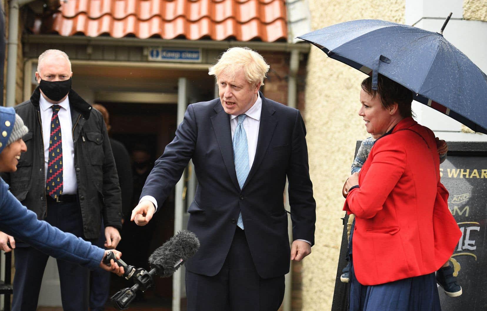 Le premier ministre britannique, Boris Johnson (au centre), échange avec une journaliste sous l'oeil de la supporter Kelly Whitfield (à droite), à Hartpool vendredi.