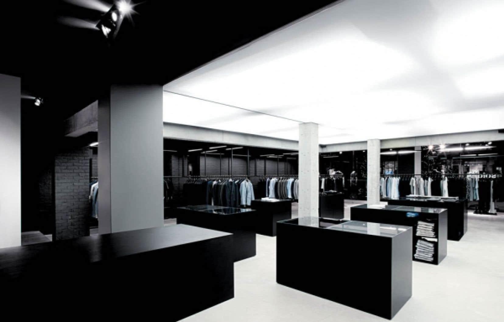 Les présentoirs cubiques en acier peint noir ponctuent l'espace comme des troncs d'arbres d'un autre ordre ayant poussé sur un sol en béton.<br />