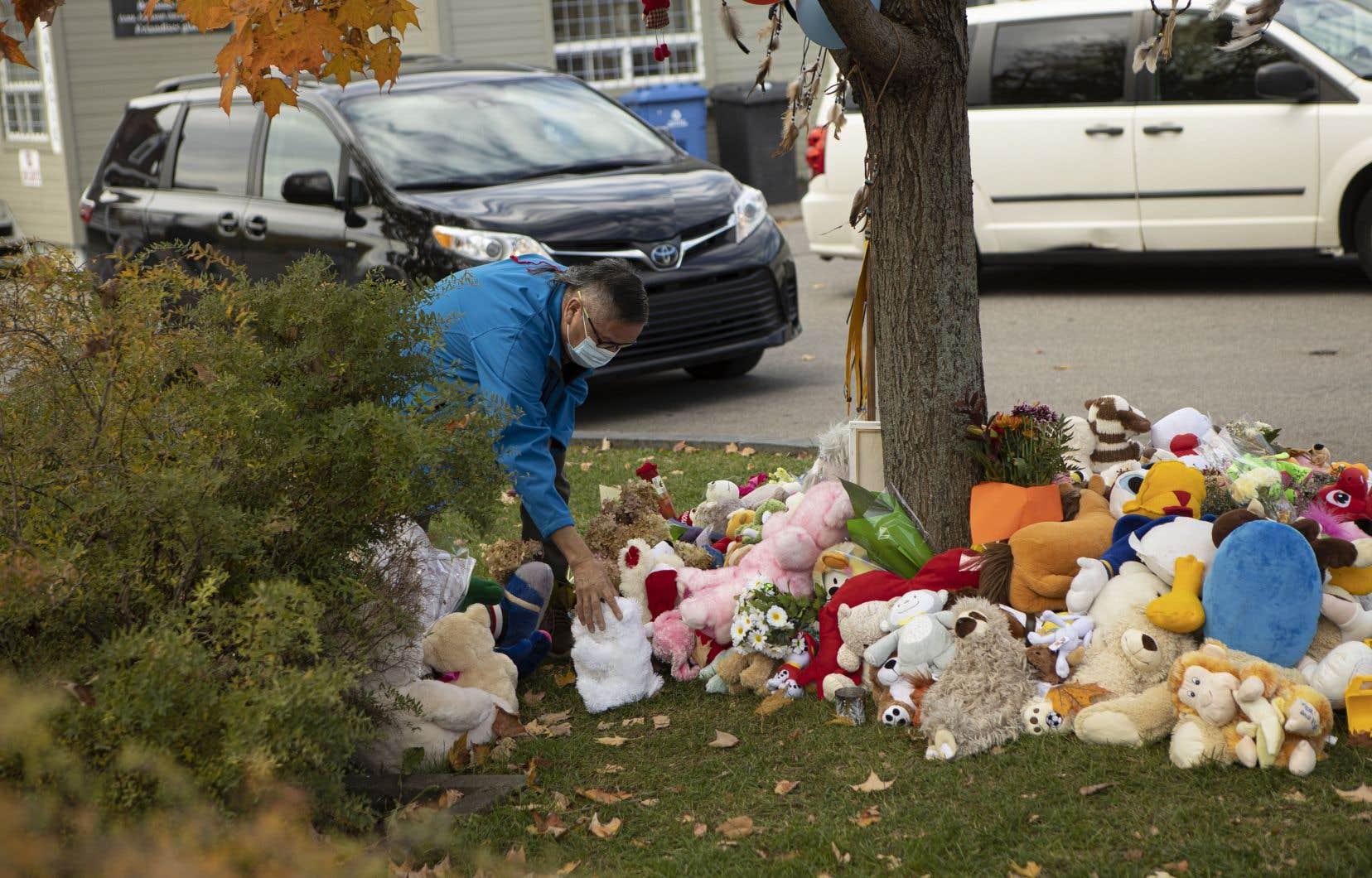 Un homme vient déposer un jouet en peluche sur les lieux du drame, survenu à Wendake en octobre 2020.