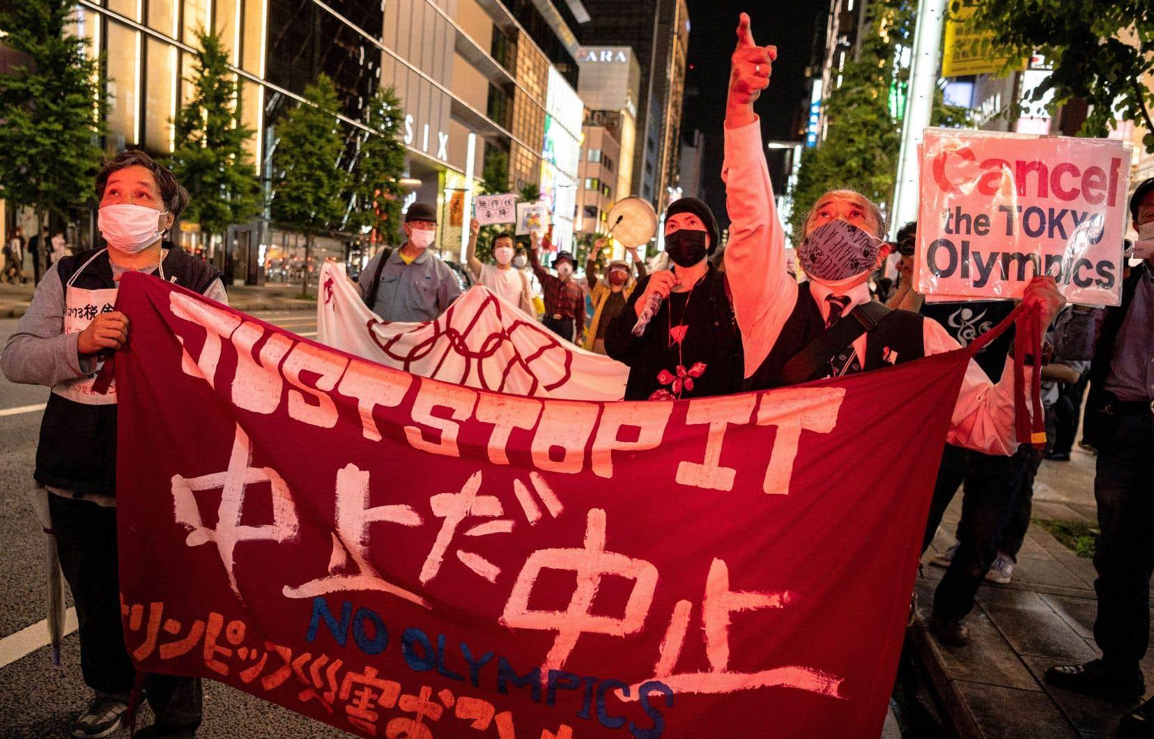 Des opposants à la tenue des Jeux olympiques manifestaient à Tokyo, lundi. Il n'est pas rare que la venue des Jeux olympiques soulève une certaine contestation dans les pays hôtes, mais cette fois, le phénomène a une tout autre ampleur.