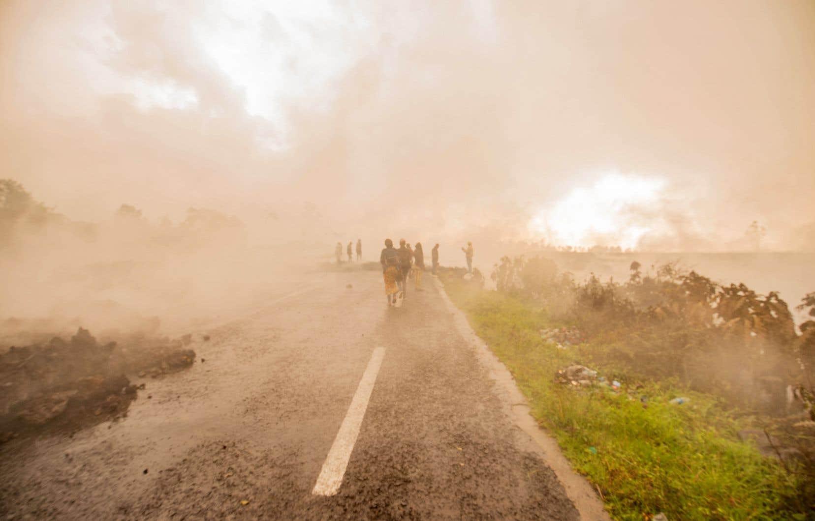 Lundi, la lave rocheuse noirâtre était encore chaude, de la fumée se dégageant par endroits. Des piétons s'aventuraient sur la lave, malgré les risques liés aux vapeurs toxiques, traversant la route là où elle a été ensevelie.