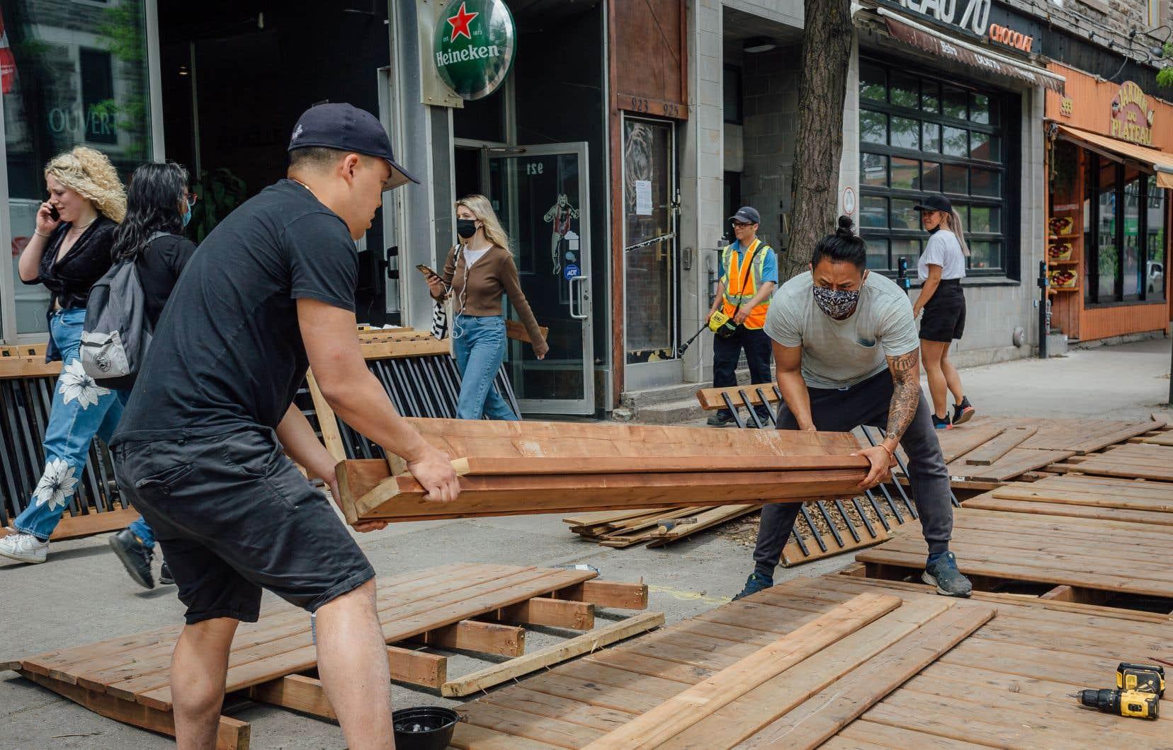 L'équipe du restaurant Le Mékong, à Montréal, prépare la terrasse qui pourra accueillir la clientèle.