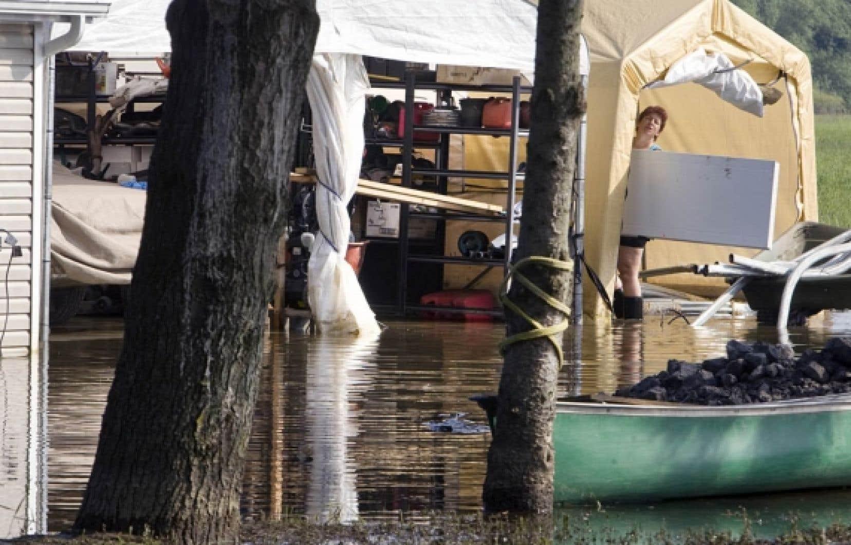 Une habitante de Saint-Blaise tente tant bien que mal de s'occuper de sa maison inondée. <br />