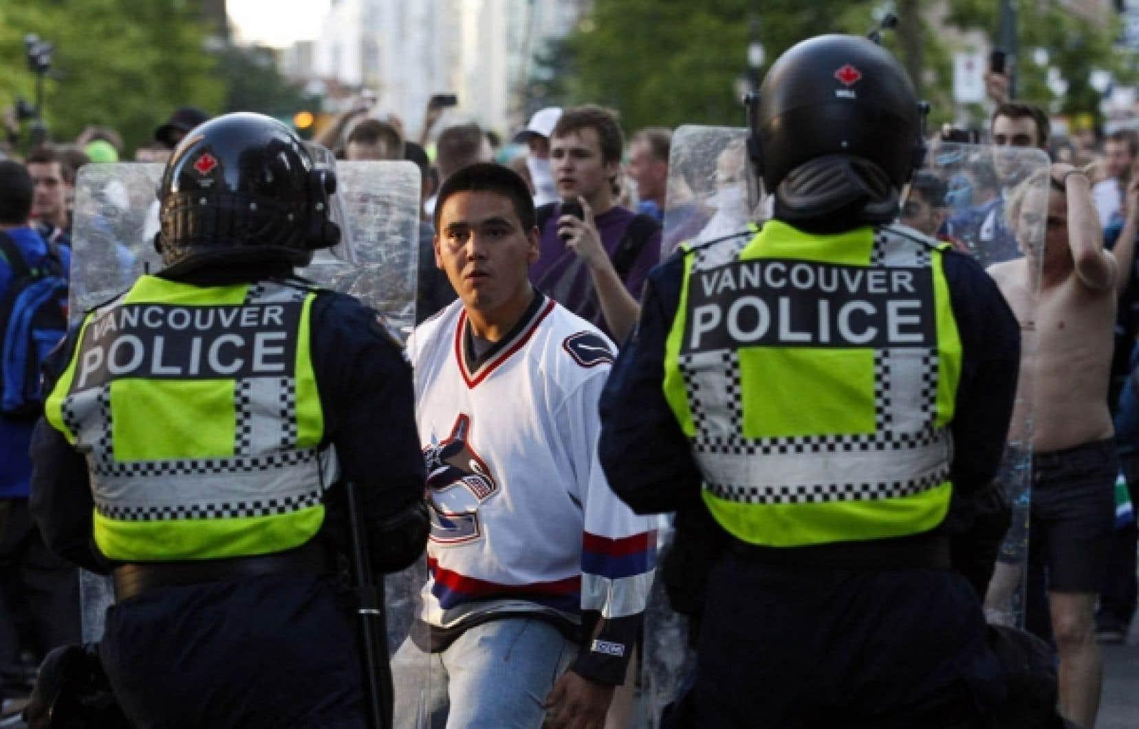 Un partisan des Canucks de Vancouver affronte des policiers après la défaite de son équipe aux mains des Bruins de Boston, mercredi dernier.