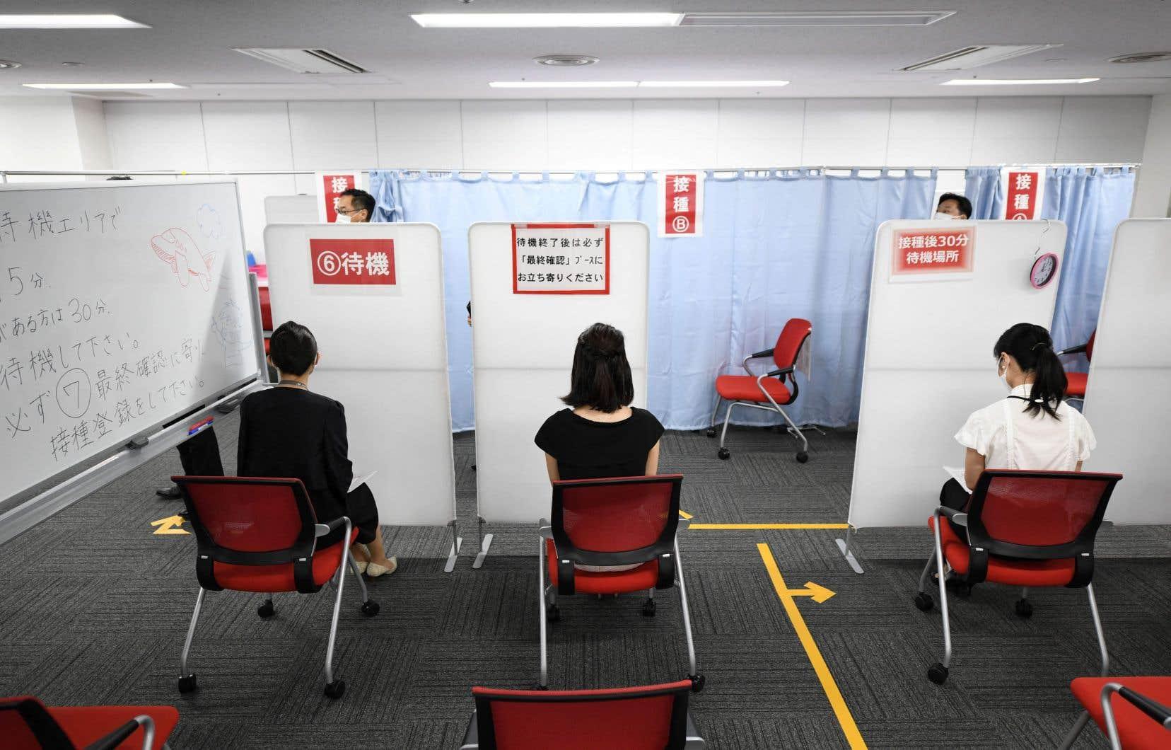 Des membres du personnel de cabine de Japan Airlines participent au premier jour de la campagne de vaccination en milieu de travail de la compagnie, à l'aéroport Haneda de Tokyo.
