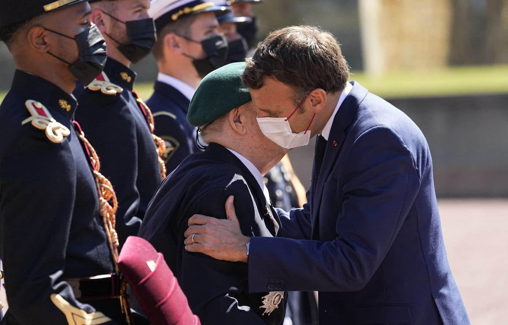 Emmanuel Macron a salué deux anciens combattants de la Deuxième Guerre mondiale en leur faisant la bise.Le leader français portait un masque, mais pas les deux hommes âgés.