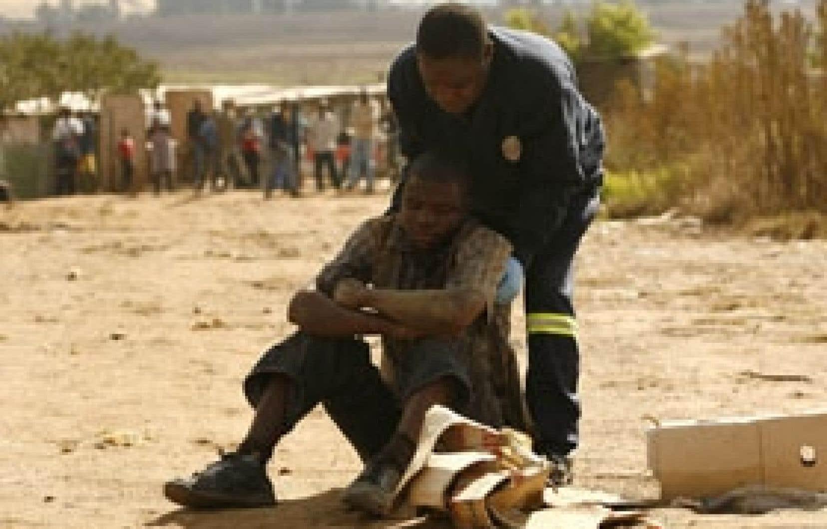 Ce policier a porté secours hier à un homme blessé au cours des violences à Johannesburg.