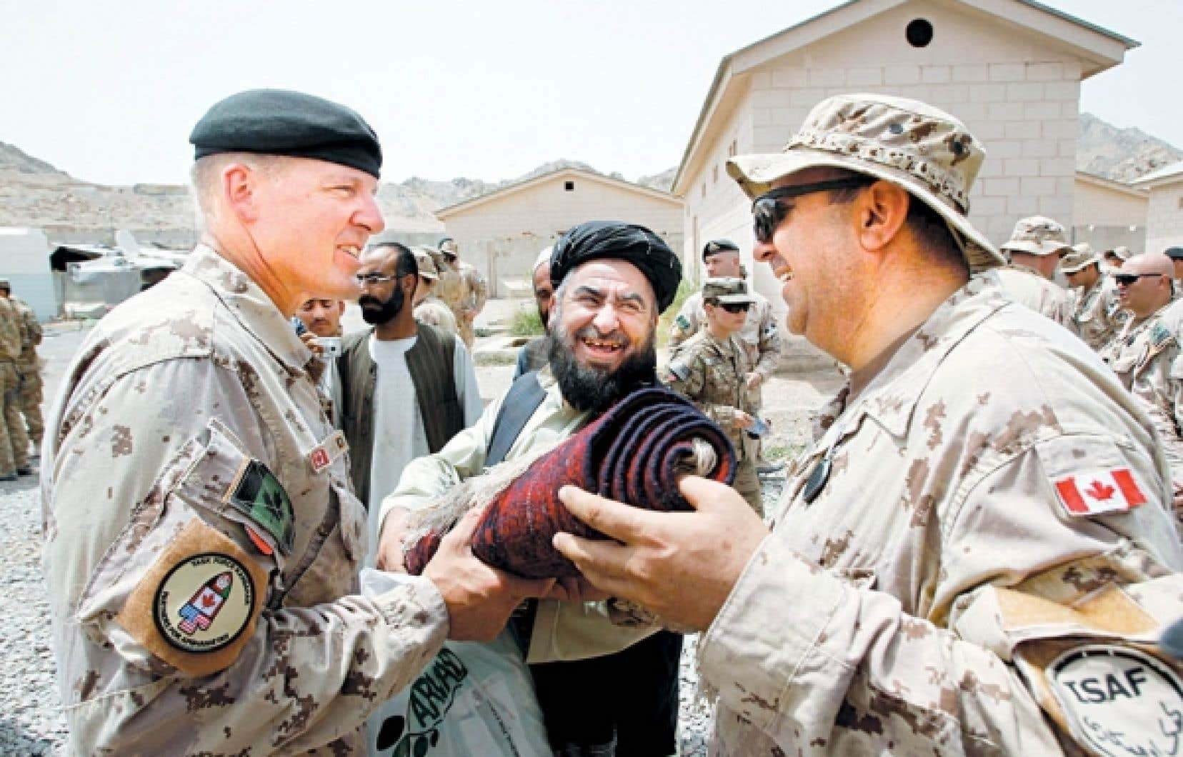 Le gouverneur du district de Panjwaii, Haji Faluddin Agha, a fait cadeau d'un tapis au brigadier-général canadien Dean Milner (à gauche), au cours de la cérémonie qui a marqué hier la fin de la mission de combat canadienne dans la province de Kandahar, en Afghanistan.<br />
