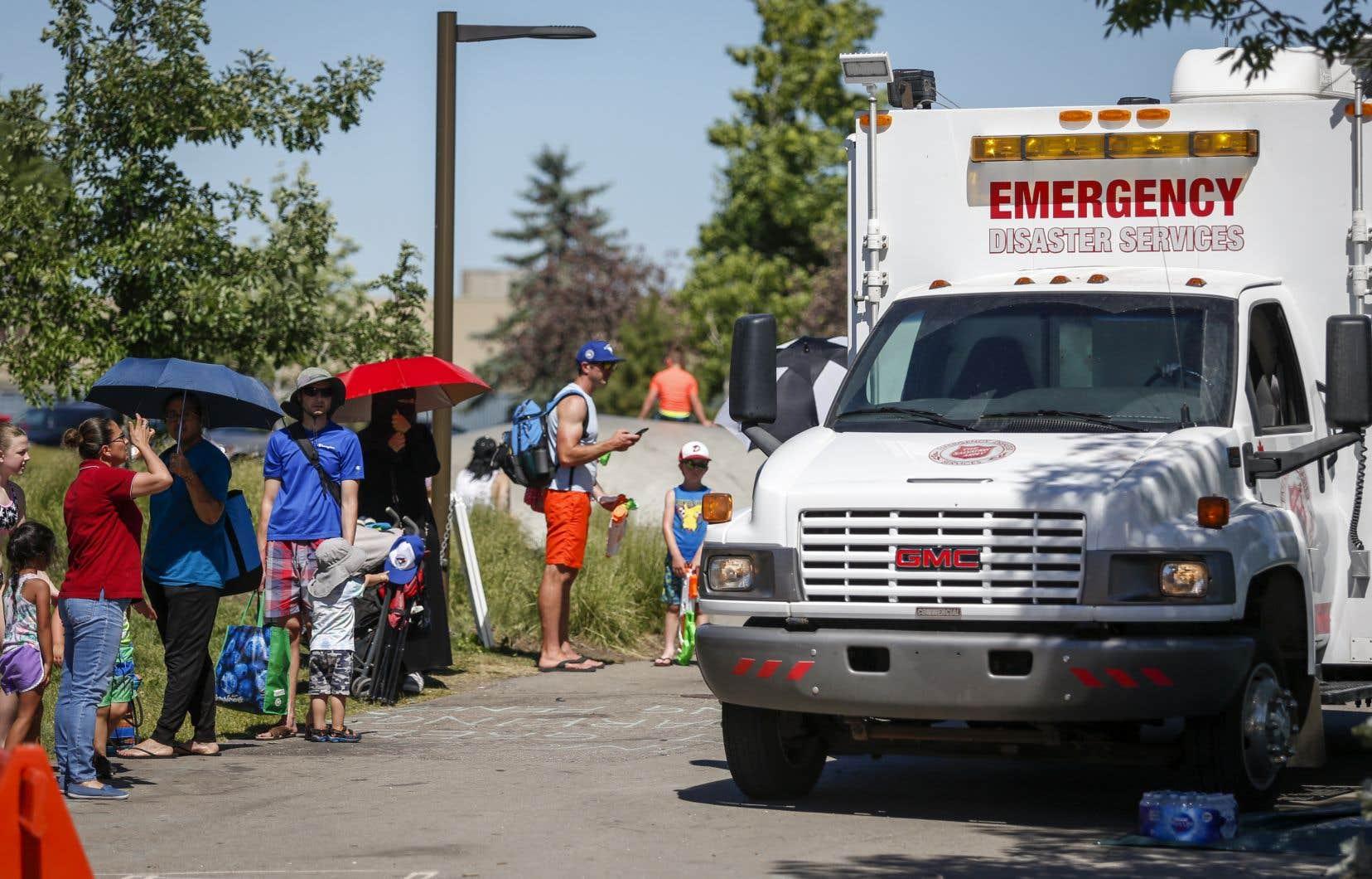Un véhicule SMU de l'Armée du Salut est utilisé comme station de refroidissement à l'entrée d'un parc aquatique à Calgary où les gens font la file pour aller se rafraîchir.