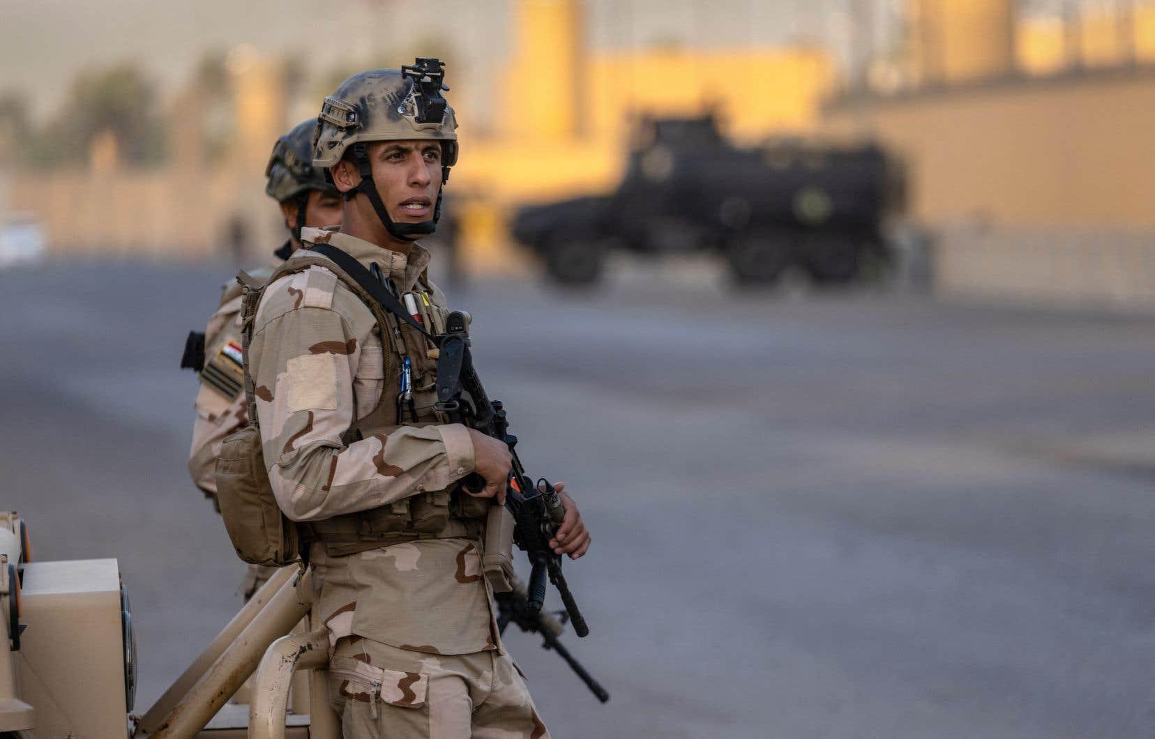 Des soldats montent la garde devant l'ambassade américaine située à Bagdad.