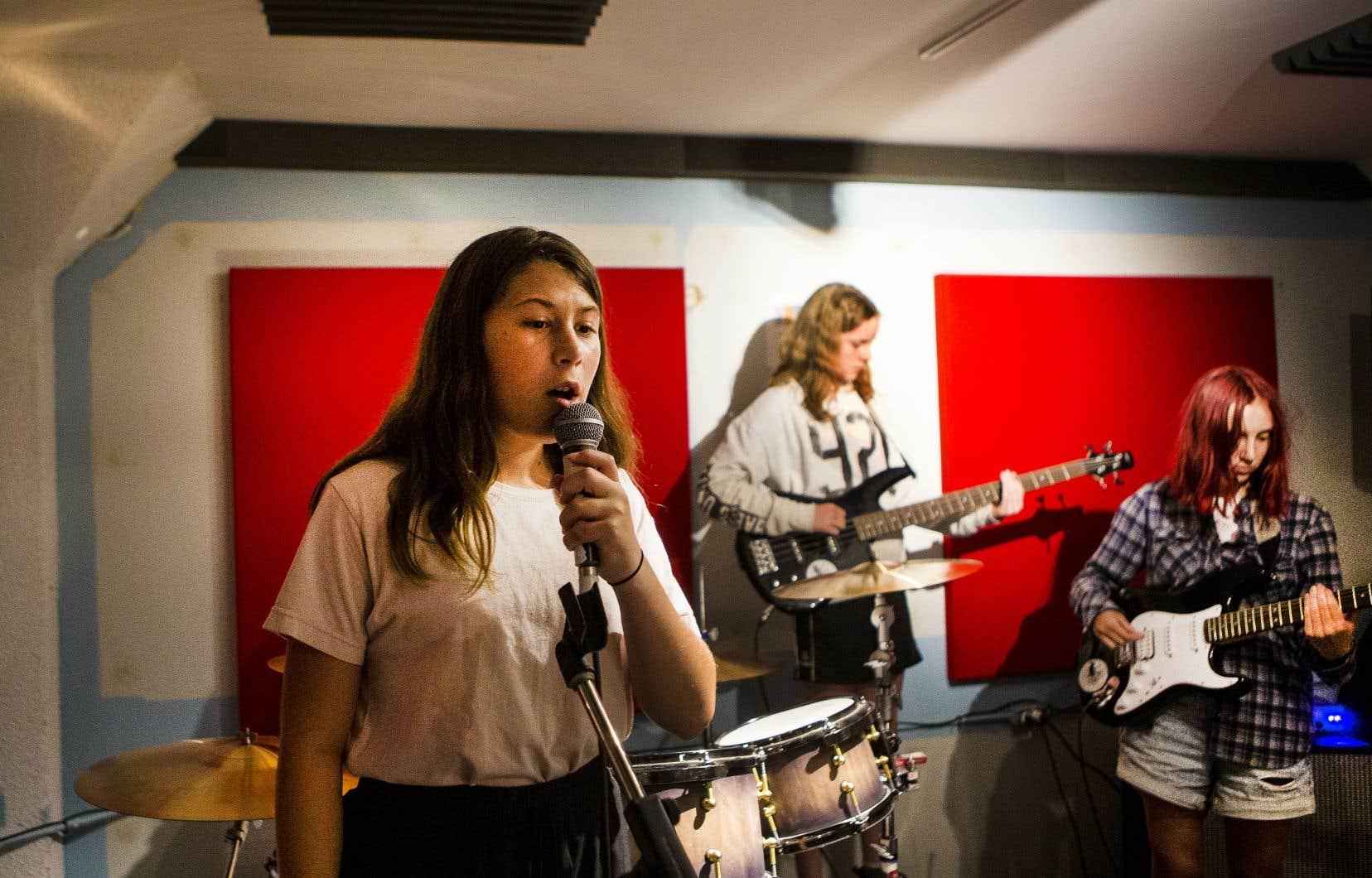 Lancée au début de l'été, à Verdun, l'École du rock de Montréal propose aux jeunes de 7 à 17 ans de découvrir l'univers de ce style musical. Sur la photo, Maolie Lacombe au chant, Ophélie Séguin à la basse et Noëlle West à la guitare, plus tôt cette semaine, lors d'une session musicale.