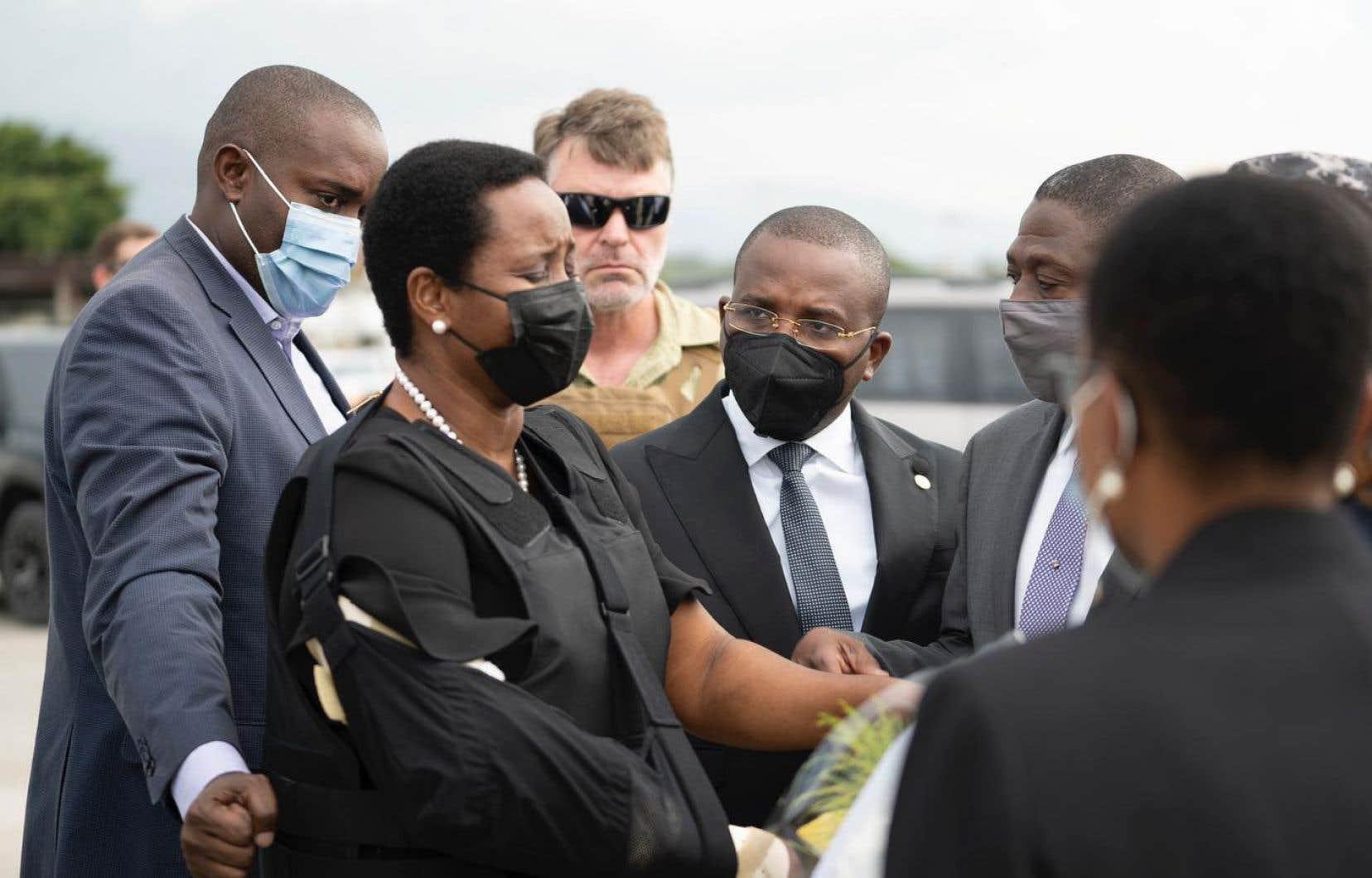 Le bras droit en écharpe, gilet par balles sur ses vêtements noirs, Martine Moïse, 47ans, a été placée sous la protection d'agents de sécurité.