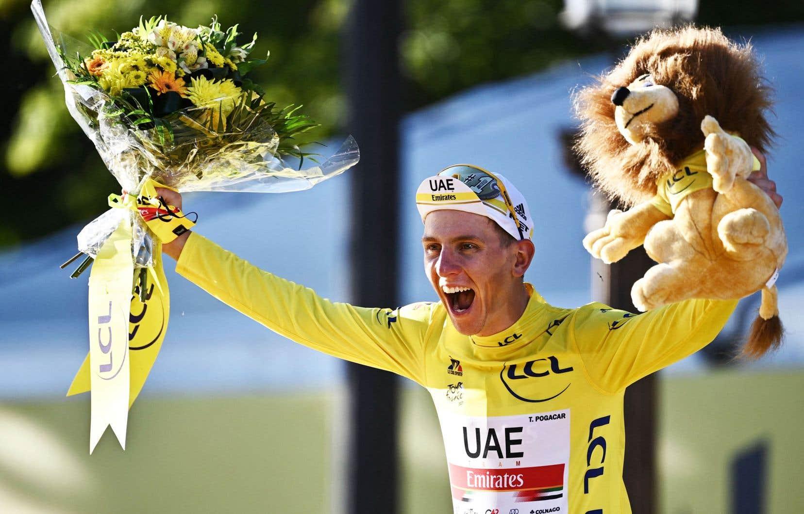 Le vainqueur Tadej Pogacar de Slovénie célèbre son maillot jaune de leader du classement général sur le podium à la fin de la 21e et dernière étape de la 108e édition du Tour de France.