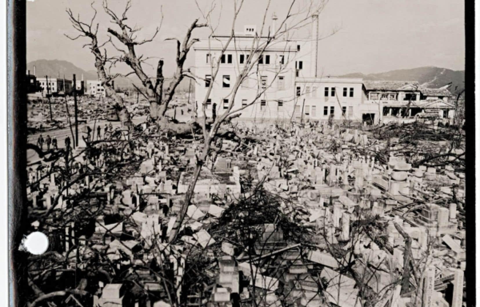 Pierres tombales renversées dans un cimetière appartenant au temple Kokutai, à Hiroshima, après l'explosion de la bombe atomique, le 6 août 1945. En arrière-plan, l'édifice de la Banque nationale du Japon. Photo prise par l'armée de l'air des États-Unis, le 5 novembre 1945.<br />