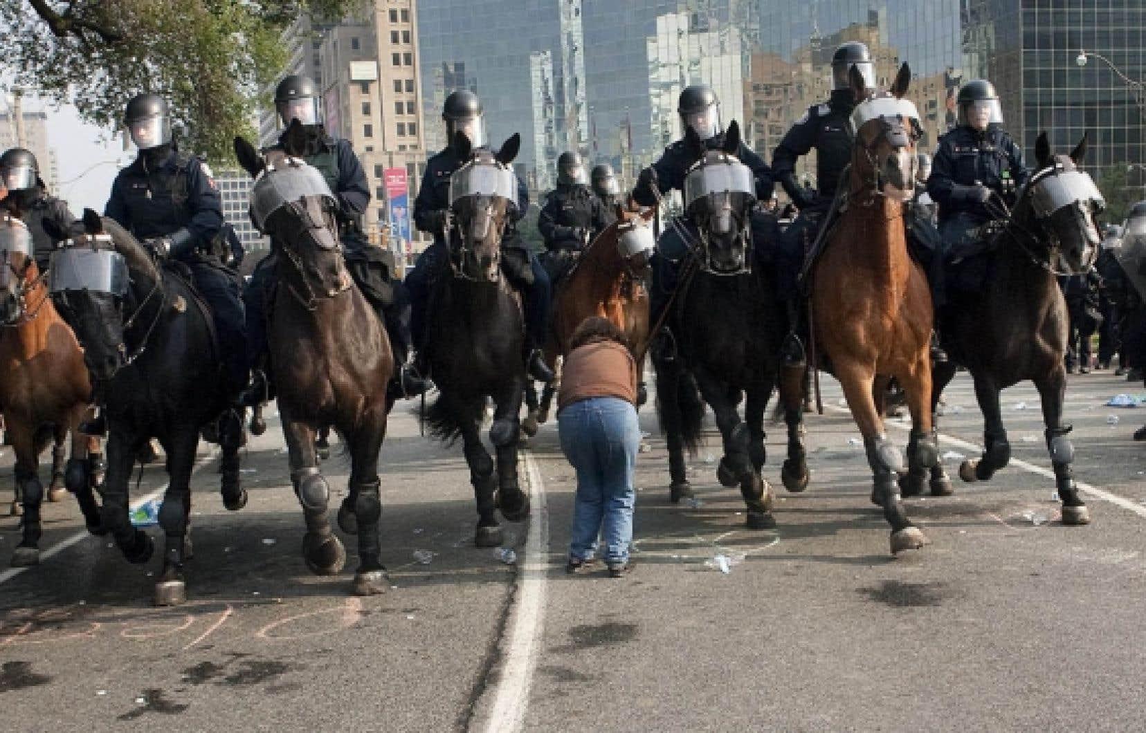 Le juge Melvyn Green écrit que «la seule agression physique collective ou organisée à cet endroit ce soir-là a été celle perpétrée par les policiers chaque fois qu'ils avançaient vers les manifestants». Sur la photo: des policiers montés et une manifestante lors du G20 à Toronto en juin 2010.<br />