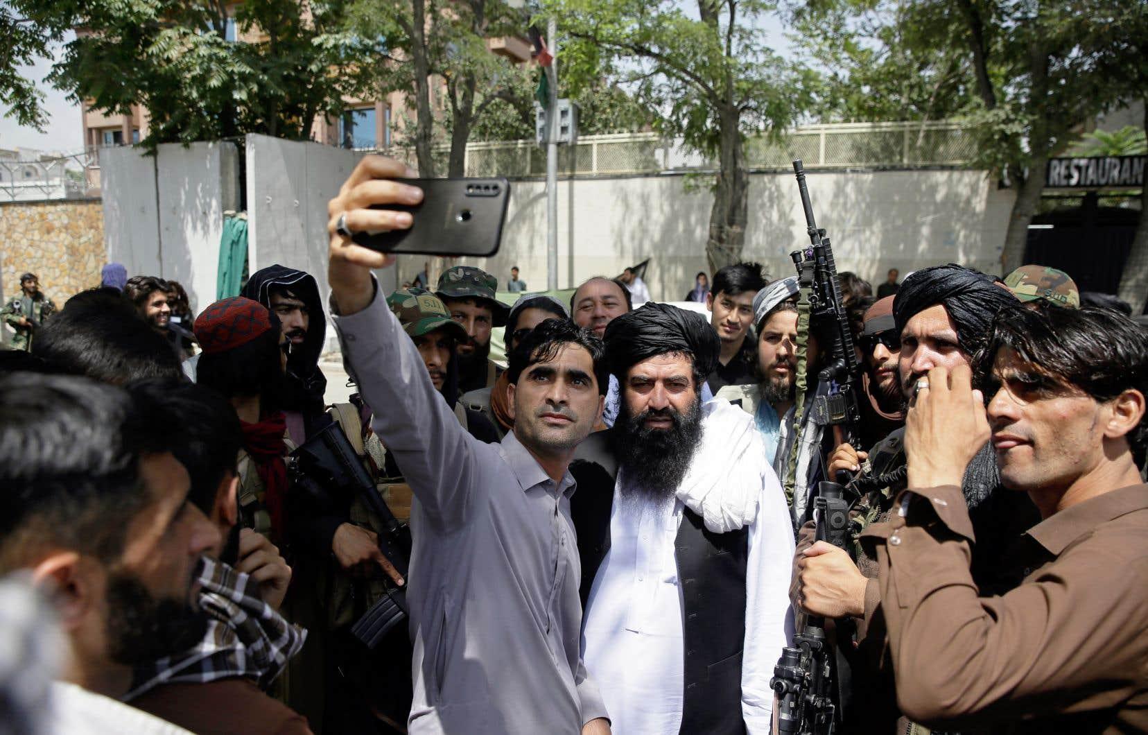 Un Afghan prenait un égoportrait avec des talibans en patrouille jeudi, à Kaboul.