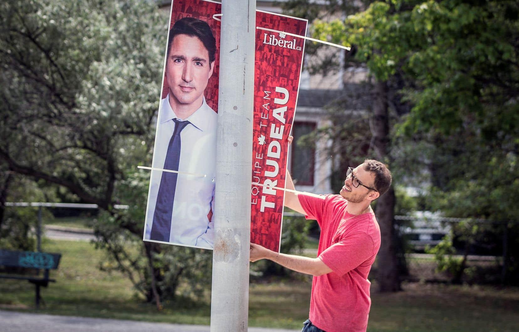 Un bénévole posait une pancarte électorale à Longueuil, mardi.