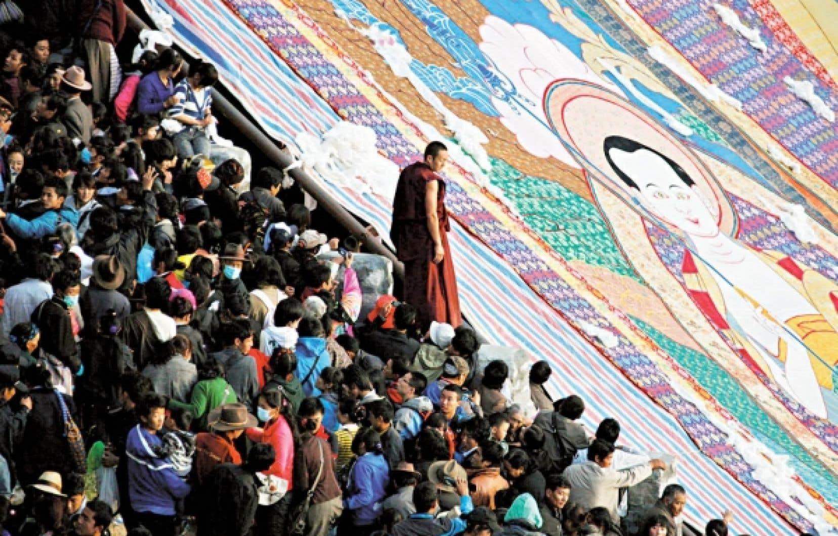 Malgré les exactions du gouvernement chinois, le bouddhisme tibétain résiste. Sur la photo, un moine boudhiste se tient entre les fidèles et un thangka (broderie religieuse) géant déployé au début de cette semaine au monastère de Drepung, près de Lhasa, dans la Région autonome du Tibet.<br />