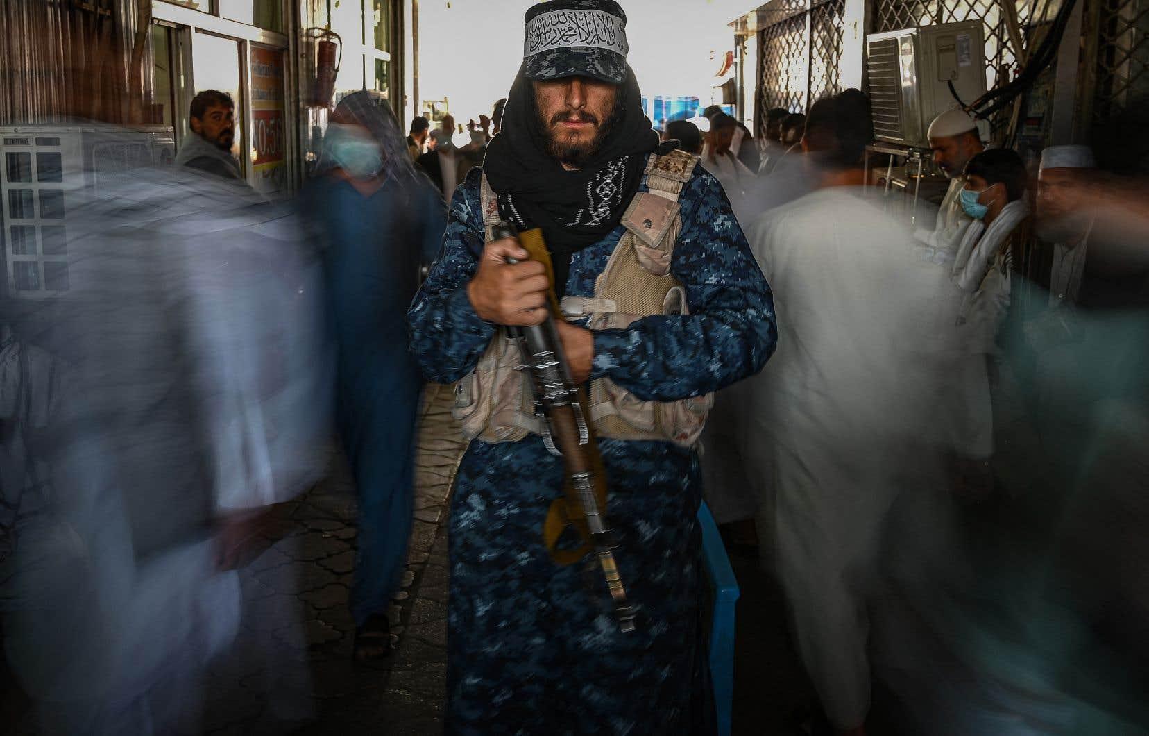 Un combattant taliban monte la garde alors que les gens passent devant lui dans un marché à Kaboul.