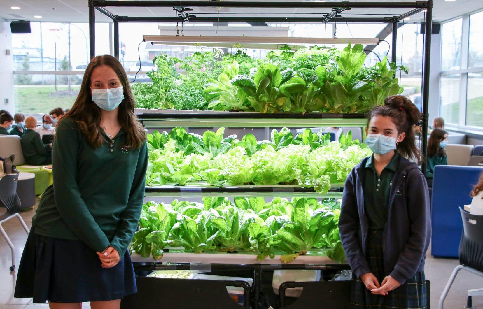 Chloé Delonca et Penelope Papadakis, deux étudiantes du collège Notre-Dame-de-Lourdes, devant la serre hydroponique où sont cultivées laitues et fines herbes.
