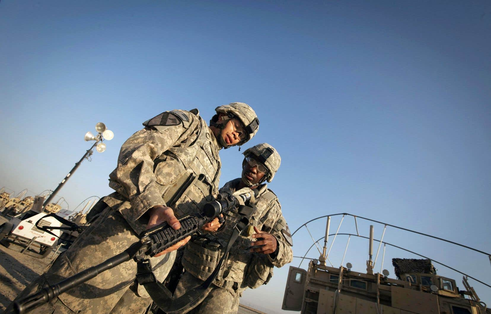 Des soldats américains déchargent leurs armes après avoir traversé la frontière koweïtienne dans le cadre du dernier convoi militaire américain à quitter l'Irak le 18 décembre 2011.
