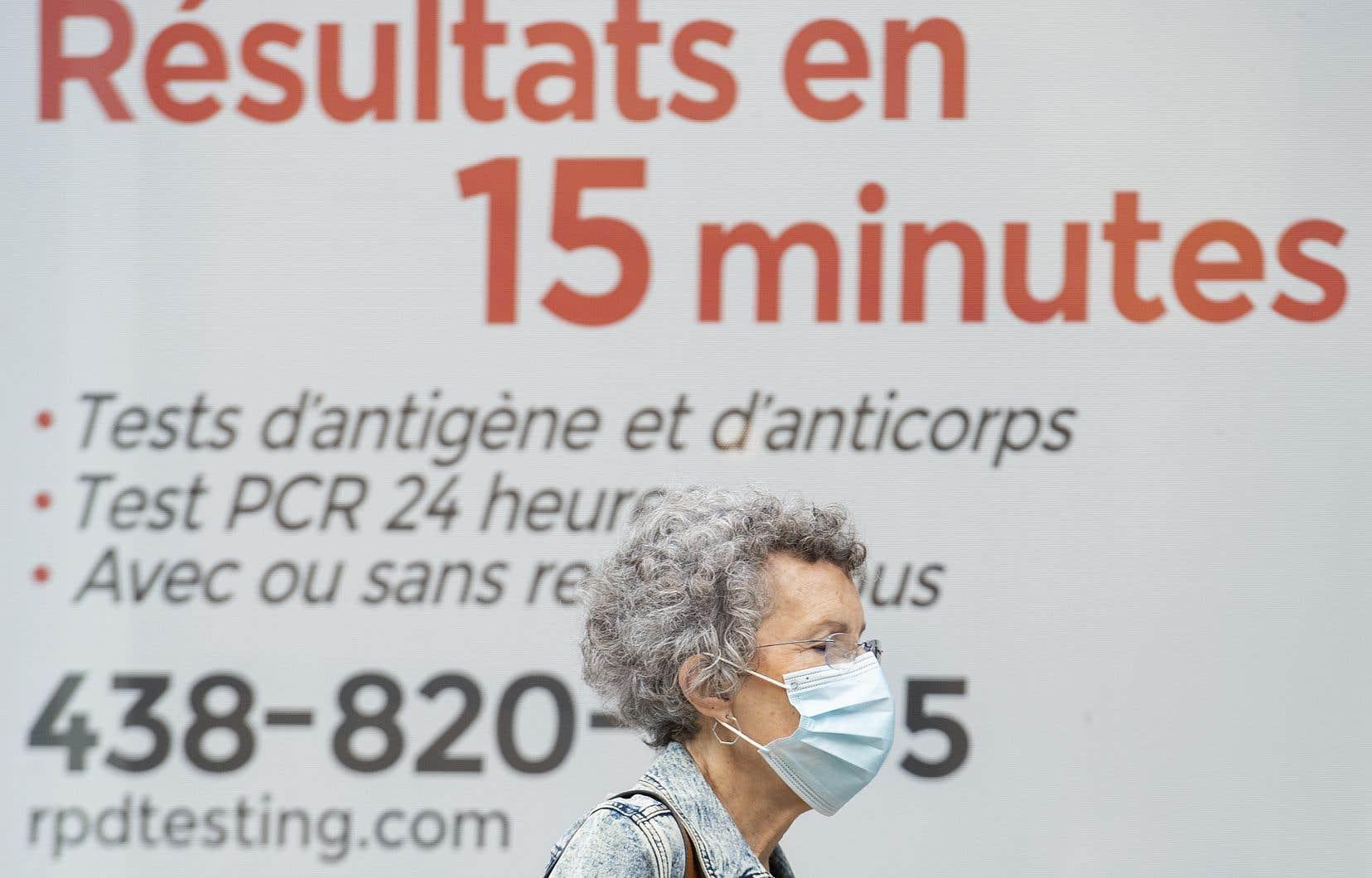 Une femme passe devant une entreprise de test rapide COVID-19 à Montréal.