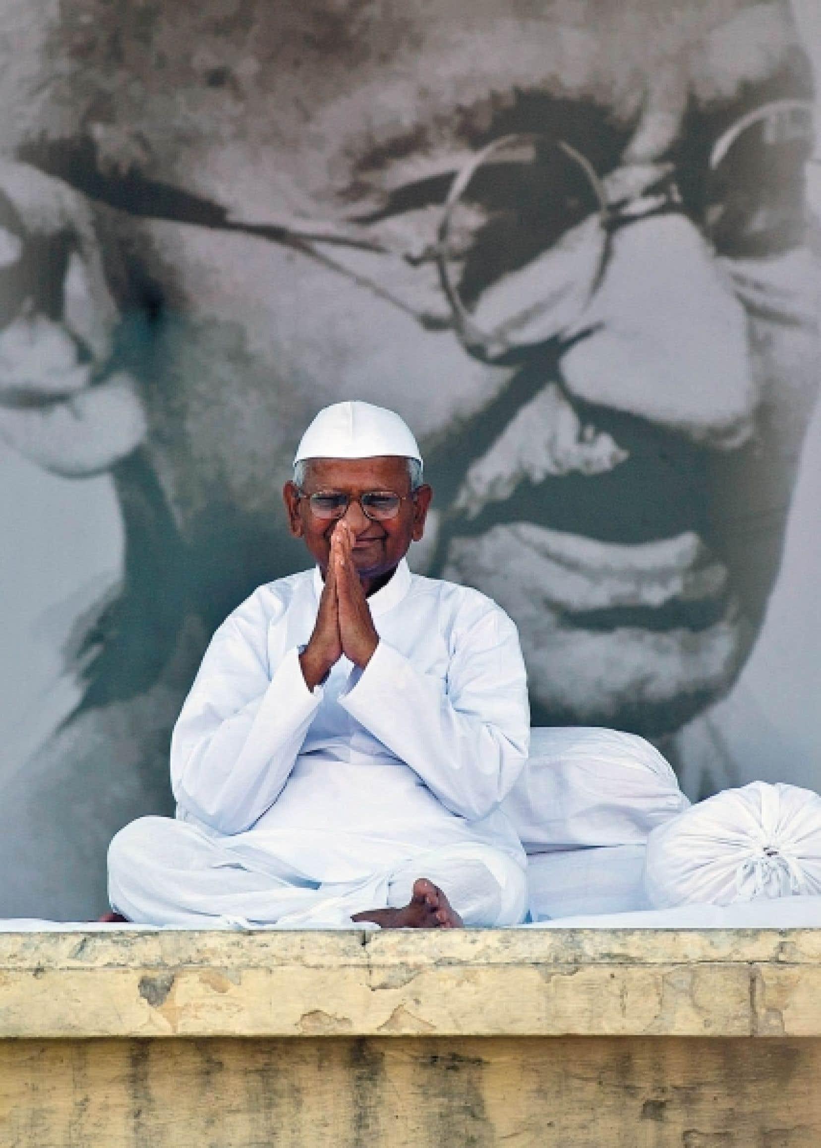 Anna Hazare au cours d'un jeûne de 13 jours qu'il a accompli à New Delhi, fin août, dans le cadre de sa croisade contre la corruption. En arrière-plan, une photo du Mahatma Gandhi.<br />